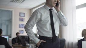 Gelukkige zakenman die goed nieuws op telefoon ontvangen, succesvolle bedrijfwelvaart stock footage