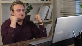 Gelukkige zakenman, die handen opheffen die laptop, het vieren overwinning bekijken stock footage