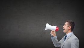 Gelukkige zakenman die in kostuum aan megafoon spreken Stock Afbeelding