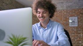 Gelukkige zakenman die met krullend groot haar over overwinning, winnaarzitting bij lijst met laptop, modern bureau toejuichen stock video