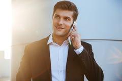 Gelukkige zakenman die op de telefoon in openlucht spreken stock afbeeldingen