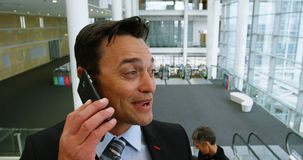 Gelukkige zakenman die op de telefoon spreken terwijl op roltrap 4k stock video