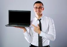 Gelukkige zakenman die zich met laptop bevinden stock afbeelding