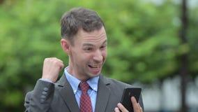 Gelukkige zakenman gebruikend telefoon en in openlucht wordend goed nieuws stock video