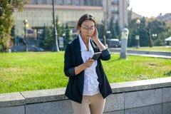 Gelukkige zakenman in kostuum met laptop in citybusinesswoman in pak die zich in de stad met een mobiele telefoon bevinden royalty-vrije stock foto's