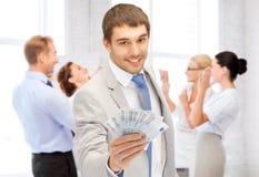 Gelukkige zakenman met contant geldgeld in bureau Stock Afbeelding