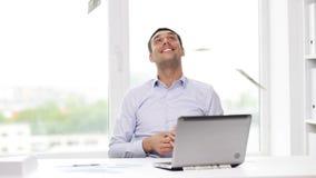 Gelukkige zakenman met geld en laptop in bureau stock footage