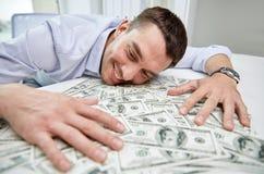 Gelukkige zakenman met hoop van geld in bureau royalty-vrije stock afbeelding