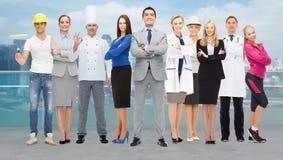 Gelukkige zakenman over professionele arbeiders Stock Foto's