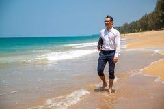 Gelukkige zakenman in overhemd met laptop en met glazen die op het strand lopen stock foto's