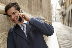 Gelukkige Zakenman Using Mobile Phone in Straat stock fotografie