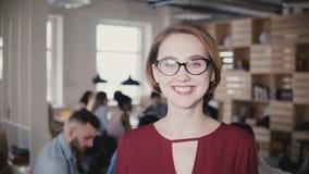Gelukkige zekere Europese jonge onderneemster die bij camera glimlachen Het zekere vrouwelijke chef- stellen op bureauachtergrond stock video