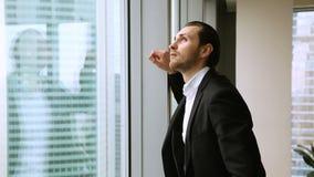 Gelukkige zekere zakenman die aan venster komen, die van grote stadsmening genieten stock videobeelden