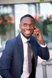 Gelukkige zekere zakenman die door celtelefoon roepen Stock Foto