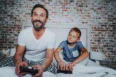 Gelukkige zoon en ouder die van hun concurrentie genieten stock foto