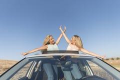 Gelukkige zuster twee in gelukkig en auto die glimlachen royalty-vrije stock foto's
