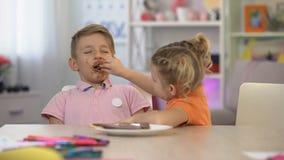 Gelukkige zuster voedende die broer met chocolade, suiker wordt gesmeerd die, bederf te veel eten stock video