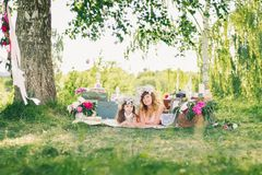 Gelukkige zusters die op een deken in openlucht op de Zonnige zomer liggen Royalty-vrije Stock Afbeeldingen