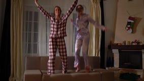 Gelukkige zusterstweelingen in pajams die op de laag in een comfortabele woonkamer springen en pret als in kinderjaren hebben ver stock videobeelden
