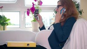 Gelukkige zwangere bedrijfsvrouw met het beeld die van de ultrasone klankfoto celtelefoon roepen stock videobeelden