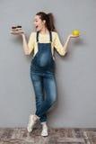 Gelukkige zwangere dame die zoete cake en appel houden stock afbeeldingen