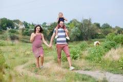 Gelukkige zwangere familie die op een gang lachen stock foto