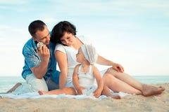Gelukkige zwangere familie met een dochter op het strand. Stock Afbeelding