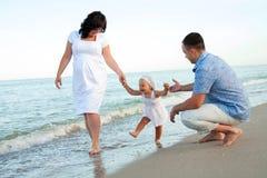 Gelukkige zwangere familie met een dochter op het strand. Stock Afbeeldingen