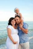 Gelukkige zwangere familie met een dochter op het strand. Royalty-vrije Stock Foto