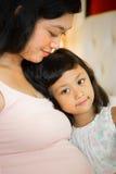 Gelukkige zwangere moeder en dochter stock foto's