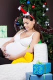 Gelukkige zwangere vrouw dichtbij de Kerstmisboom Royalty-vrije Stock Afbeelding