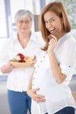 Gelukkige zwangere vrouw die chocolade eet Royalty-vrije Stock Foto's