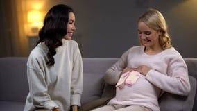 Gelukkige zwangere vrouw die kleine sokken op haar buik, babydouche met vriend houden stock foto's
