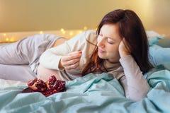 Gelukkige zwangere vrouw die op bed rusten, die granaatappel eten stock afbeeldingen