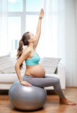 Gelukkige zwangere vrouw die op fitball thuis uitoefenen Stock Afbeeldingen