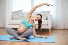 Gelukkige zwangere vrouw die thuis uitoefenen Royalty-vrije Stock Foto's