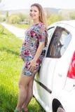 Gelukkige zwangere vrouw die zich dichtbij auto bevindt Stock Afbeeldingen