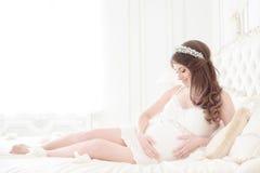 Gelukkige zwangere vrouw in een licht binnenland stock fotografie