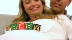 Gelukkige zwangere vrouw met babykubussen op buik stock footage