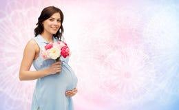 Gelukkige zwangere vrouw met bloemen wat betreft buik Stock Foto
