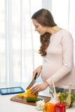 Gelukkige zwangere vrouw met het kokende voedsel van tabletpc stock fotografie