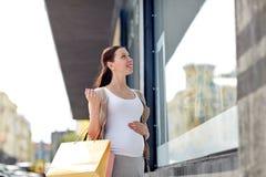 Gelukkige zwangere vrouw met het winkelen zakken bij stad stock foto