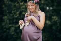 Gelukkige zwangere vrouw op een tarwegebied met baby` s schoenen stock afbeeldingen