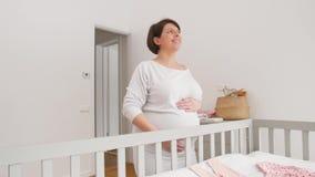 Gelukkige zwangere vrouw wat betreft haar buik thuis stock footage