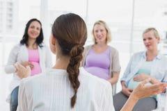 Gelukkige zwangere vrouwen die aan het gesturing van arts bij prenatale klasse luisteren stock foto
