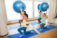 Gelukkige zwangere vrouwen die met bal in gymnastiek uitoefenen Stock Foto