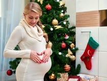 Gelukkige zwangere vrouwenzitting op vloer en wat betreft haar buik over de achtergrond van de Kerstmisboom Stock Foto