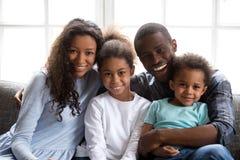 Gelukkige zwarte familie van vier die camera thuis bekijken stock foto's