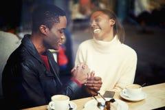 Gelukkige zwarte man en vrouw die prettijd hebben samen terwijl in restaurant na het wandelen in koude de winterdag warm word, royalty-vrije stock foto's