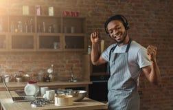 Gelukkige zwarte mens die aan muziek luisteren en in keuken dansen stock foto's